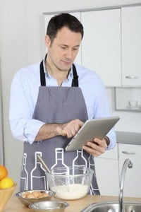 Man on iPad in kitchen while cooking - ©Depositphotos/Goodluz